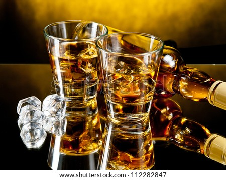 Two glasses of whiskey on the rocks with a bottle behind - stock photo