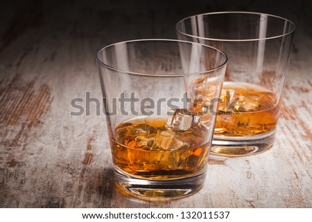 two glasses of whiskey over wooden background - stock photo