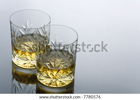 Two Glasses  of Whisky on a Reflective Surface with Copy Space - stock photo