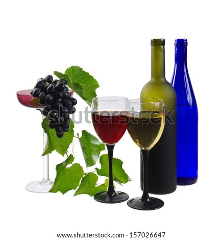 Two glasses of white and red wine, two bottles and grapes  - stock photo