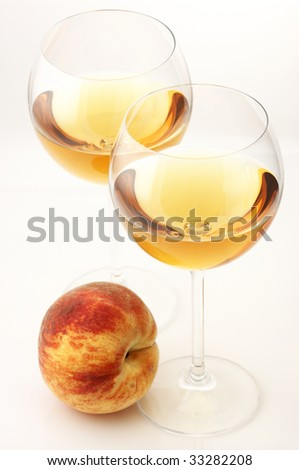 Two glasses of white wine and peach on white background. - stock photo