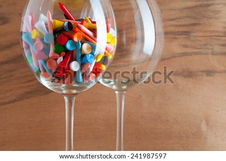 Two glasses of wine and golf tees on the wooden background from real wood veneer with interesting growth - stock photo