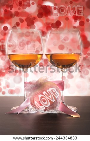 Two glasses of wine and pink heart with love on bokeh background. Valentines day. - stock photo