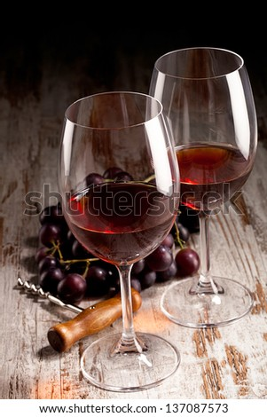two glasses of wine, grapes and corkscrew - stock photo