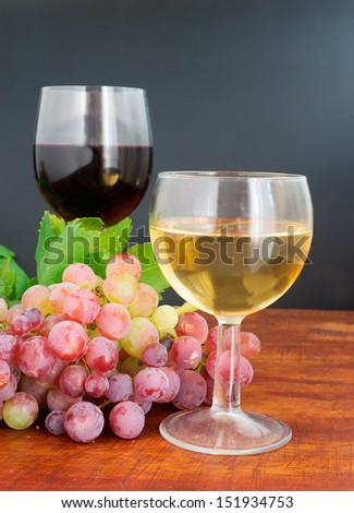 two glasses of wine on a wooden table - stock photo