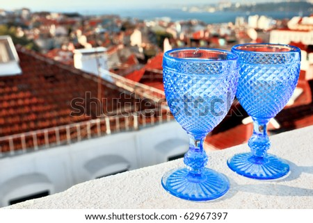 Two glasses of wine on the roof of the town. - stock photo