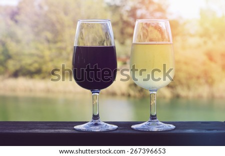 Two glasses of wine, white and red, on wooden rail with country rural scene in background with applied retro style filters and lens flare. - stock photo