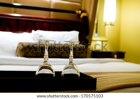 Two glasses on the double bed as romantic concept - stock photo