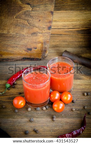 two glasses tomato juice pepper cherry on a brown wooden background with pepper and cherry - stock photo