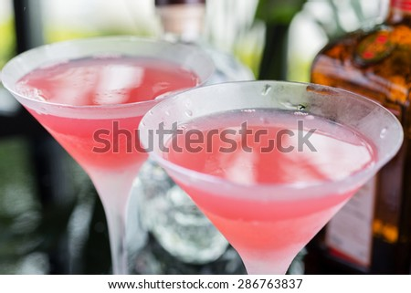 Two glasses with bright refreshing cocktail Cosmopolitan with the decor of orange slices on a table in a restaurant with beautiful bokeh. Soft focus. - stock photo
