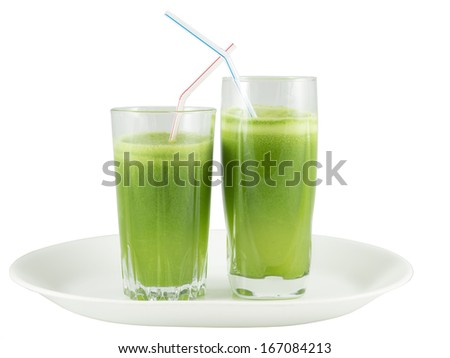 Two glasses with green vegetable juice on a plate against white background - stock photo