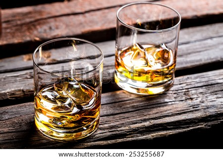 Two glasses with ice and whiskey - stock photo