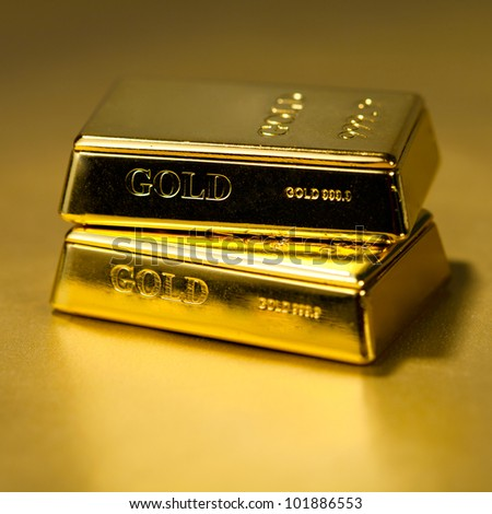 Two Gold bullions on golden background - stock photo