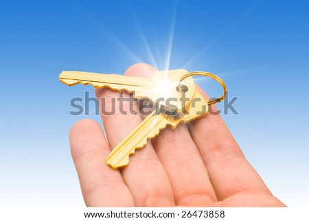 two gold keys on a palm over blue background - stock photo