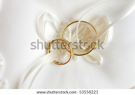 two gold wedding rings on a pillow - stock photo