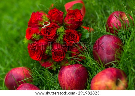 Two gold wedding rings on bridal bouquet with scarlet roses and fresh apples on green grass - stock photo