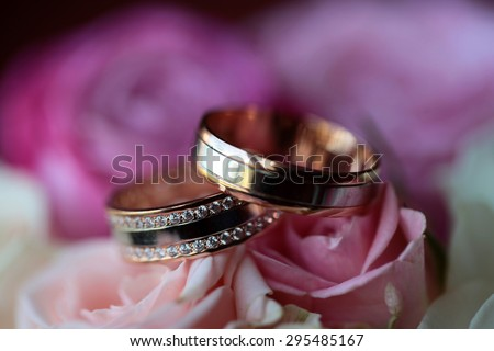 Two gold wedding rings with diamonds on bouquet of fresh flowers of pink and white roses closeup, horizontal picture - stock photo