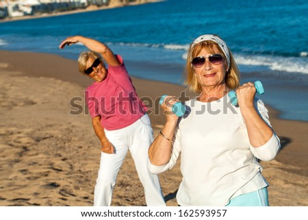 Two golden age women working out together on beach.  - stock photo