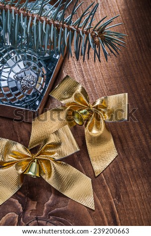 two golden christmas bows with little bells and mirror disco balls and pinetree branch on old wooden board - stock photo