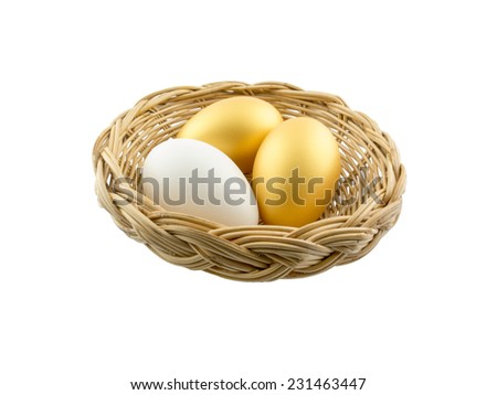 two golden eggs with one white in the basket - stock photo
