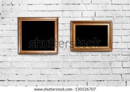 two golden frames on brick wall background - stock photo