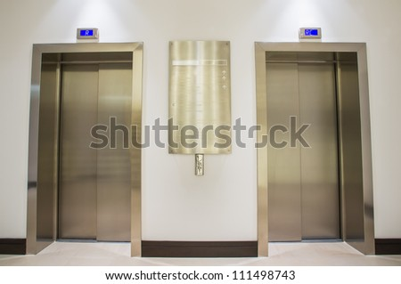 Two golden lifts situated on the ground floor of the company. - stock photo