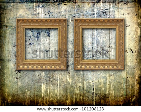 two golden vintage frames on a grunge scratched and painted wood plank wall - stock photo
