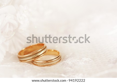 Two golden wedding rings with seamless flower decorations. There is a place for text (copy space). Can be used in invitation, advertisement, as a nice romantic background or other - stock photo