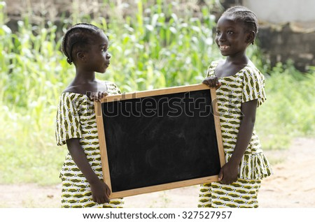 Two Gorgeous African Girls Holding Up a Chalkboard Copy Space. Beautiful girls holding up and showing a black blackboard. Plenty of copy space to add your text. Two black schoolgirls holding a symbol. - stock photo