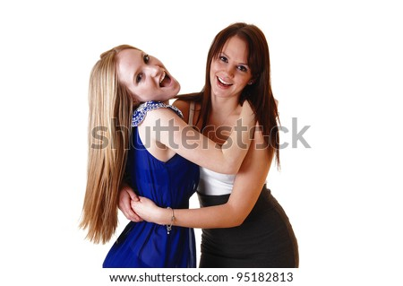 Two gorgeous young woman hugging each other and having fun in the studio, laughing, with blond and brunette hair in a close picture. - stock photo