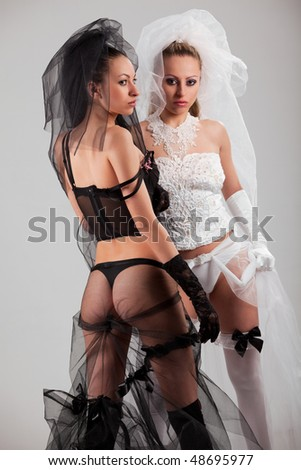 Two gorgeous young women wearing black and white lingerie - stock photo