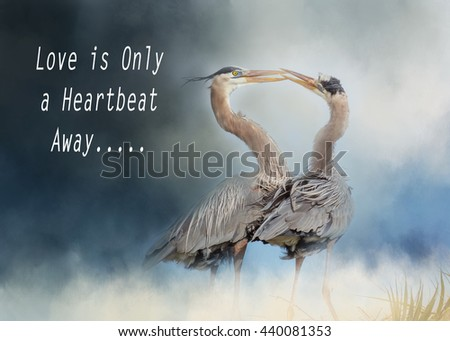 Two great blue herons on nest doing a mating ritual with inspirational quote, love is only a heartbeat away - stock photo