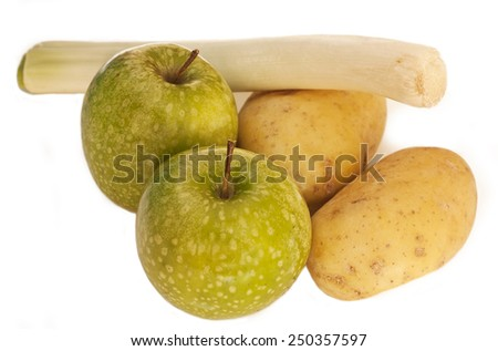 Two green apples, two potatoes and a leek on a white background - stock photo