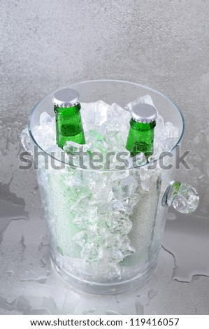 Two green beer bottles in a crystal ice bucket sitting on a wet stainless steel surface. - stock photo