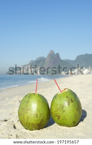 Two green coconuts on Ipanema Beach against a backdrop of Two Brothers Dois Irmaos Mountain Rio de Janeiro Brazil - stock photo