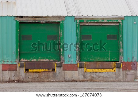 Two green painted shuttered doors for loading in a prefabricated metal clad warehouse building - stock photo