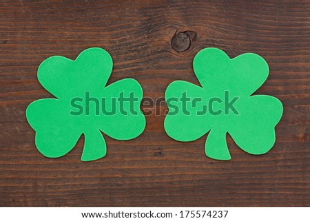 Two green shamrocks side by side on aged andmeather beaten brown knotted wood. - stock photo