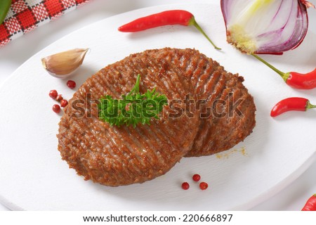 two grilled burgers with chili pepper, garlic and pink pepper - stock photo