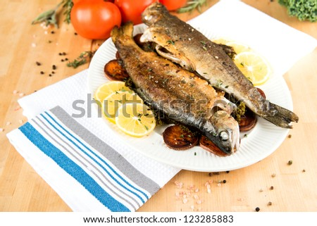 Two Grilled Fish Served with Lemon Slices and Vegetables - stock photo