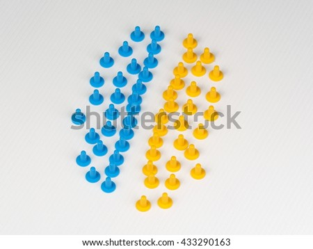 Two groups of colored plastic hat shaped parts with a gap on white - stock photo