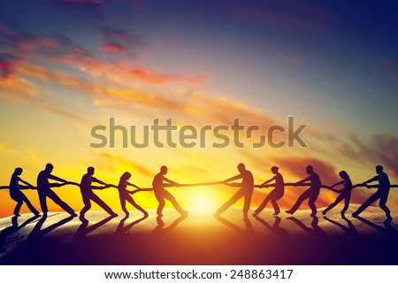 Two groups of people pulling line, playing tug of war. Competition, teamwork, strength. Conceptual - stock photo