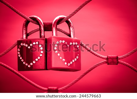 Two grungy love padlocks with heart decoration attached to the bridge in Paris. Valentine's day background. Toned photo.  - stock photo
