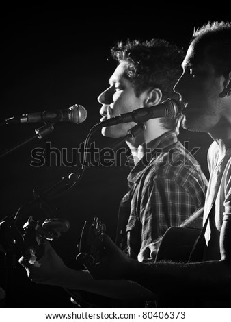 two guitar players singing and playing guitars on the stage, black and white image, for music,entrainment themes - stock photo