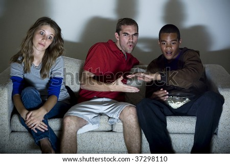 Two guys exchange low fives as the girlfriend watches in boredom. - stock photo