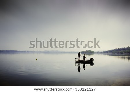 Two guys fishing on a small boat in the lake of Pusiano, Italy - stock photo