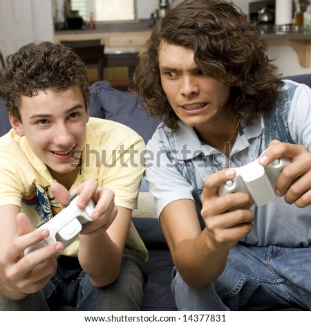 Two guys play videogames on a couch - stock photo