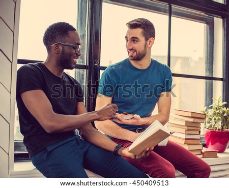 Two guys reading a book in a room. - stock photo