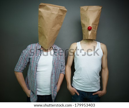 Two guys standing in front of camera in paper bags celebrating fool�¢??s day - stock photo