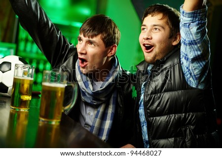Two guys watching sports at bar and rejoicing - stock photo