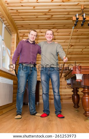 two guys with a billiard cue express joyful emotions in a game anticipation - stock photo